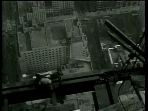 construction workers cross beams at dangerous heights to build the empire state building - ニュース映画点の映像素材/bロール