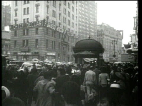 universal newsreel. pedestrians on an american sidewalk read about war news on a scrolling electronic sign and at newspaper stands. - 1939 stock-videos und b-roll-filmmaterial