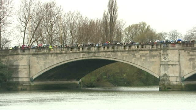 oxford beat cambridge; england: london: ext crowd lining banks of river thames in the rain to watch the oxford v cambridge university boat race /... - oxford england stock-videos und b-roll-filmmaterial