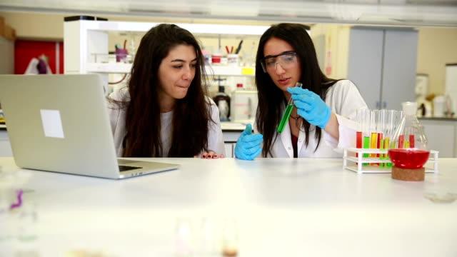 vídeos y material grabado en eventos de stock de estudiantes de investigación del laboratorio universitario de química que trabajan en clase juntos - aprendiz