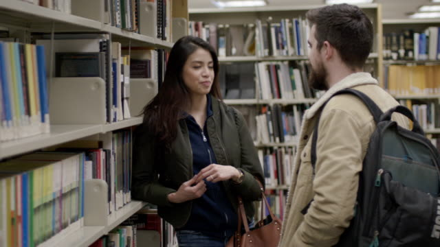 university couple talking in library - teenage couple stock videos & royalty-free footage