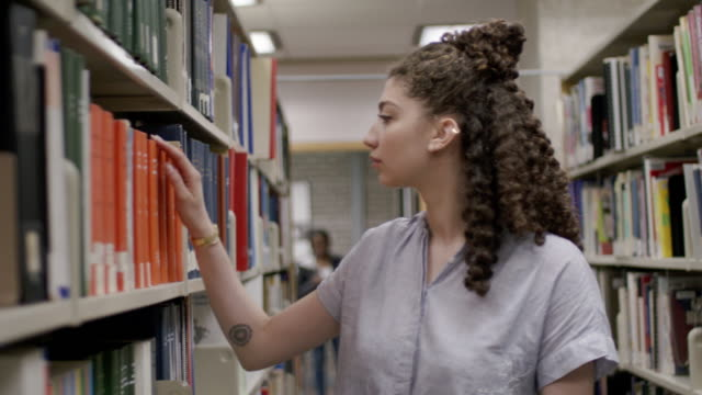 university female reading in library - library stock videos & royalty-free footage