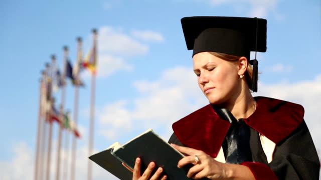university graduate mit einem buch - kopfbedeckung stock-videos und b-roll-filmmaterial