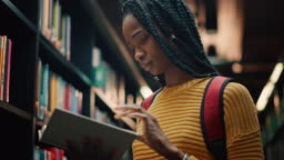 University Library: Smart Beautiful Black Girl Standing Next to Bookshelf Holding and Reading Text Book, Doing Research for Her Class Assignment and Exam Preparations. Low Angle Portrait with a Smile