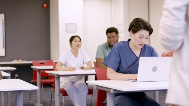 vidéos et rushes de étudiants en sciences infirmières de l'université assis dans la conférence - femmes d'âge moyen