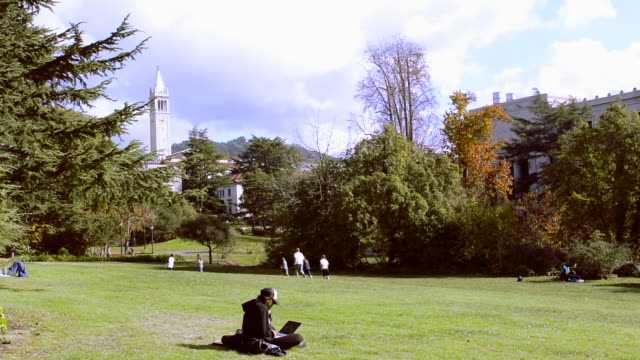 University of California at Berkeley with student on laptop while others play frisbee football with Sather Tower in background on sunny day