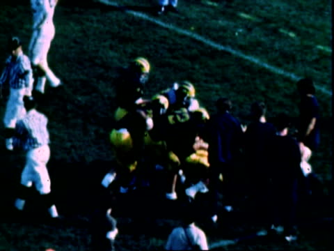 University of Michigan Wolverines quarterback DENNIS BROWN scrambling passing to JIM MANDICH for touchdown in games against rivals Michigan State...