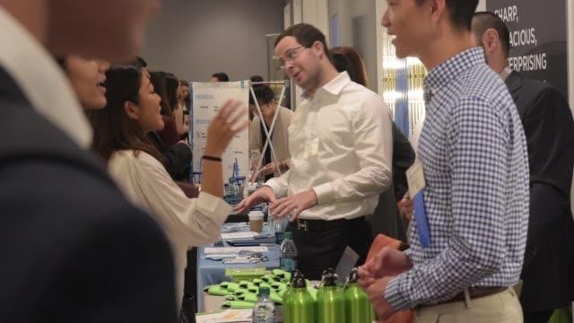 vídeos de stock e filmes b-roll de university of pennsylvania students speak with job recruiters at a career fair in at the sheraton hotel in university city philadelphia pa sept 15... - feira de emprego