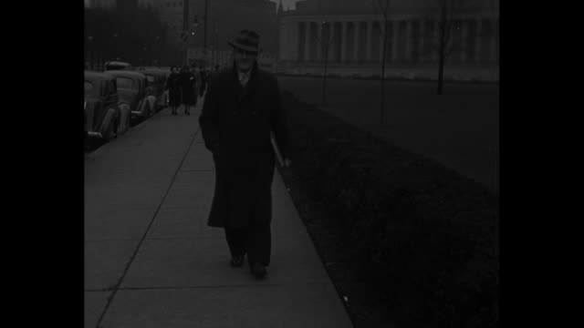 University of Pittsburgh tackle Tony Matisi walks along street on campus wearing overcoat and hat he stops / Matisi pages through notebook binder...