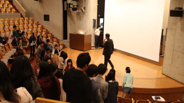 vidéos et rushes de university professor is giving handouts to students in a big lecture hall - professor