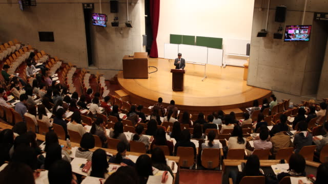 university professor standing on the auditorium stage during lecture in front of students in a big lecture hall - auditorium stock videos & royalty-free footage