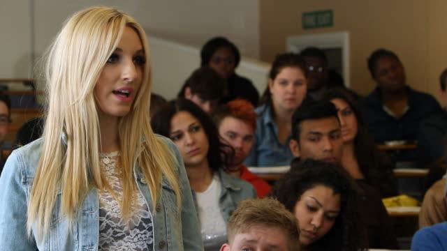 university student answers question in seminar - lecture hall bildbanksvideor och videomaterial från bakom kulisserna