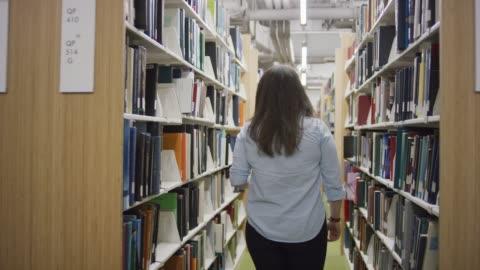 universitetsstudent söker en bok - student bildbanksvideor och videomaterial från bakom kulisserna