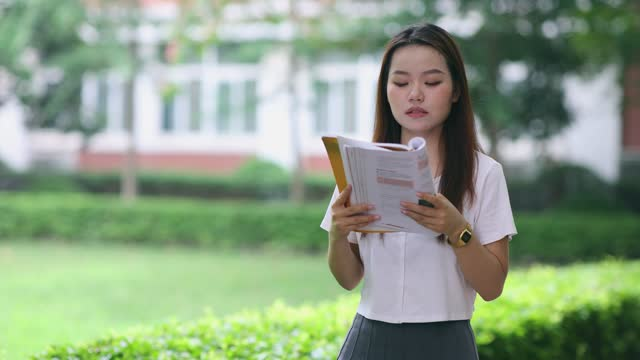 university student reading a book in campus - one teenage girl only stock videos & royalty-free footage