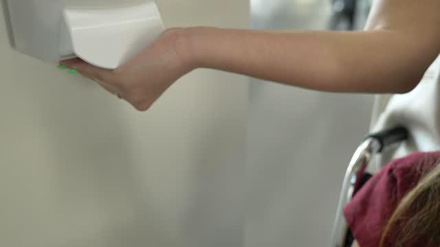 vídeos de stock e filmes b-roll de university student using hand sanitizer - professora