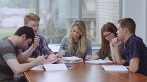 studenten, die ein gespräch an einem tisch - erwachsene person stock-videos und b-roll-filmmaterial