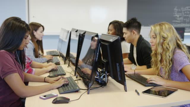 vídeos de stock e filmes b-roll de estudantes universitários em um laboratório de informática - homem e máquina