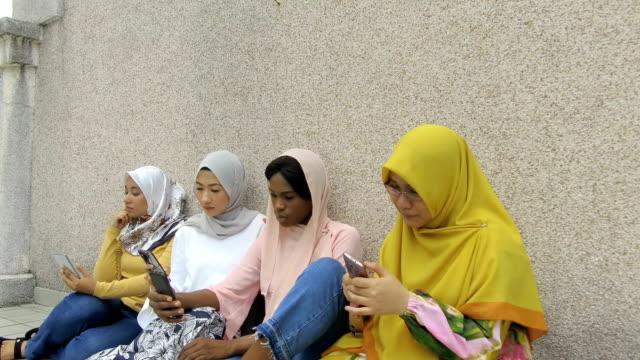 vídeos de stock, filmes e b-roll de estudantes universitários no hijab usando smartphone na faculdade com amigos - vestuário modesto