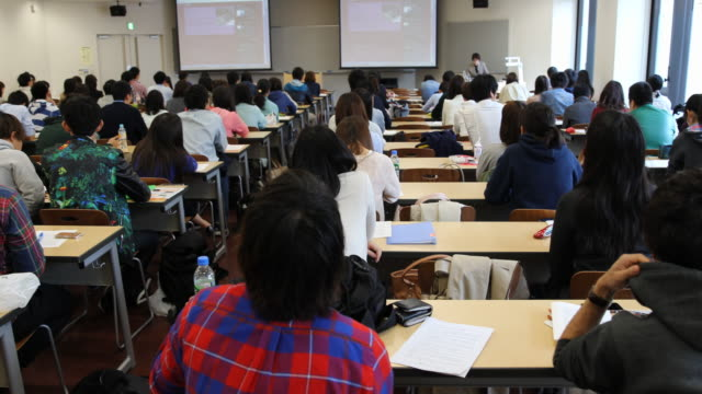 university students, seen from the back, during a presentation in a big seminar room - lecture hall stock videos & royalty-free footage