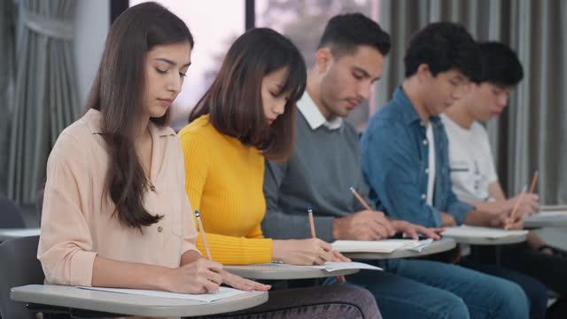 教室でノートを勉強し、書く大学生 - 民族点の映像素材/bロール
