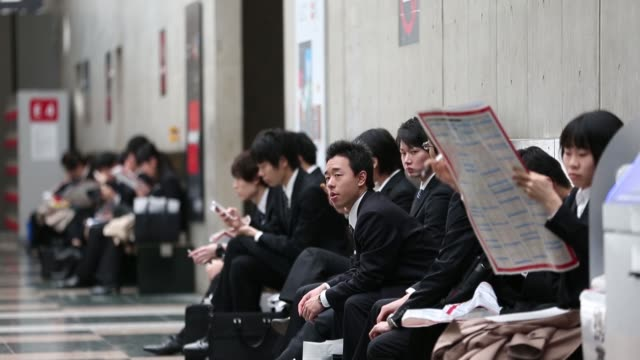 University students walk down steps at a job fair hosted by Mynavi Corp in Tokyo Japan on Sunday March 20University students fill out registration...