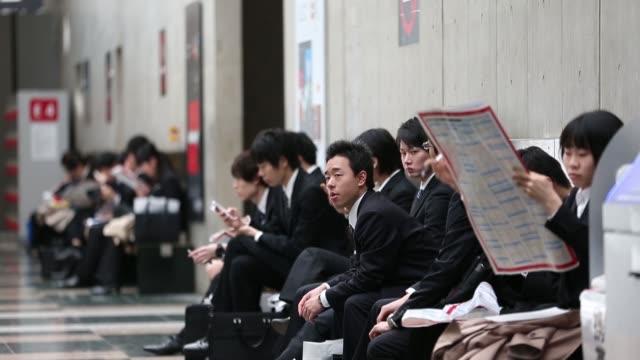 vídeos de stock e filmes b-roll de university students walk down steps at a job fair hosted by mynavi corp in tokyo japan on sunday march 20university students fill out registration... - procurar emprego
