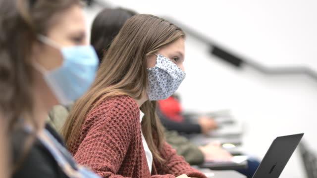 vídeos y material grabado en eventos de stock de estudiantes universitarios con máscaras en clase - universidad