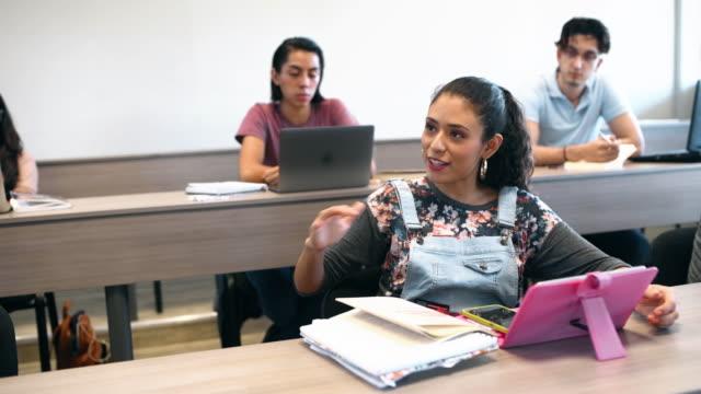 docente universitario e studenti in aula - foro video stock e b–roll