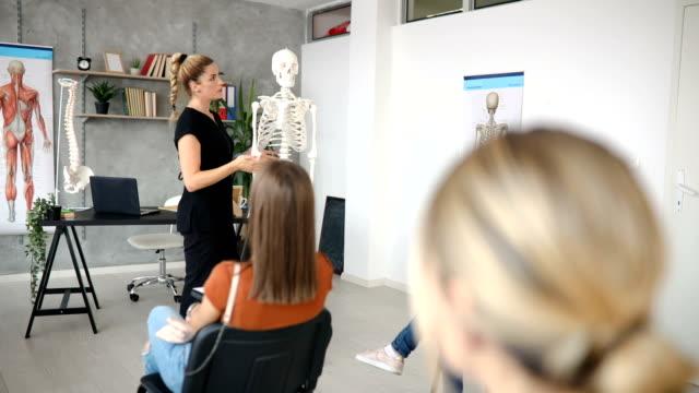 vídeos de stock e filmes b-roll de university teacher leading an anatomy class and explaining to students everything about human skeleton - anatomia