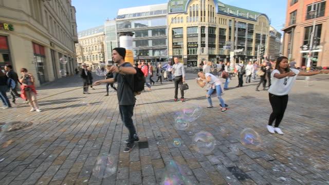 unknown street artist makes bubbles in hackescher markt, mitte - markt stock videos & royalty-free footage