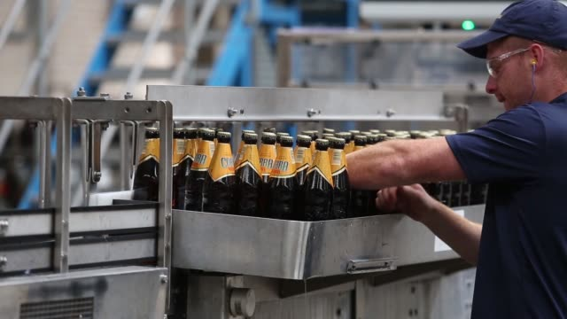 Unlabelled bottles of Cobra beer manufactured by Molson Coors Brewing Co pass along the production line ahead of labeling at the company's brewery...