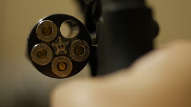 unloading ammunition into revolver - beladen stock-videos und b-roll-filmmaterial