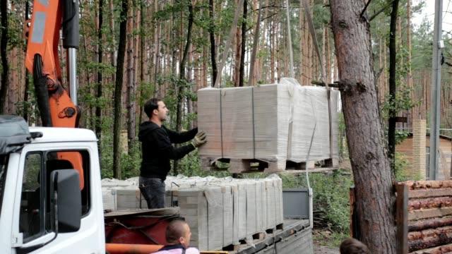 unloading bricks on the construction site. - brick stock videos & royalty-free footage