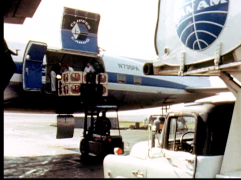 1960 MONTAGE Unloading cargo with for lift from hold of Pan Am Boeing 747 cargo plane N735PA. CU Fragile Pan American labels. Two men unloading boxes from cargo hold by hand and placing them into cart / Pakistan