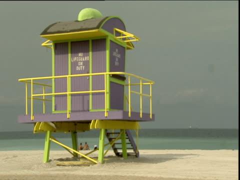unmanned lifeguard tower on empty beach sea in background miami - cabina del guardaspiaggia video stock e b–roll