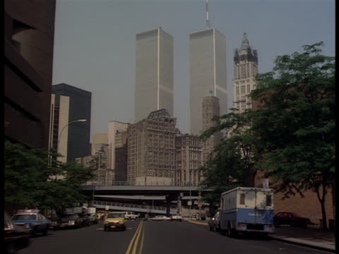 unmarked blue police car from bg , enter left into police garage / blue and white bizbar in front / pan up and zoom into windows of police station plaza / see world trade center twin towers in bg - limousine stock-videos und b-roll-filmmaterial