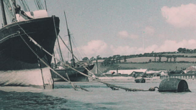 1937 montage unneeded sailing schooners beached and seabirds on the shore and pier below the village / par, england, united kingdom - stranded stock videos and b-roll footage