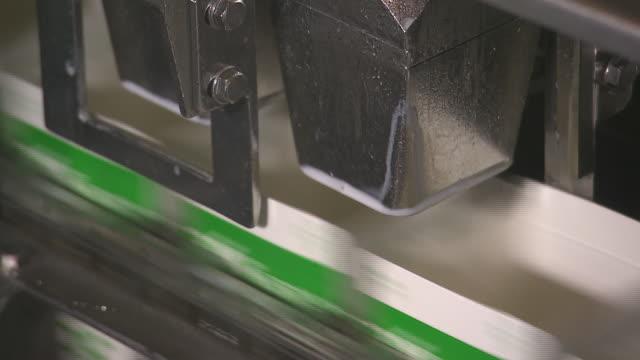 vidéos et rushes de unoccupied milk cartons moving on conveyor belt. - brique