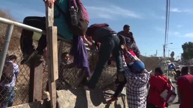 vídeos y material grabado en eventos de stock de unos 500 migrantes centroamericanos se lanzaron el domingo sobre la valla fronteriza que divide a mexico de estados unidos pero desistieron de cruzar... - ee.uu
