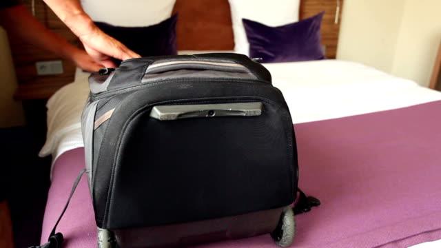 vídeos y material grabado en eventos de stock de desempacar su equipaje en el hotel - maleta