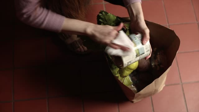 unpacking and wiping groceries - bag stock videos & royalty-free footage