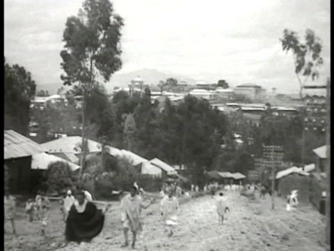 ETHIOPIA Unpaved downhill street w/ people in traditional dress walking small houses BG ITALY Italian Fascist dictator Benito Mussolini in cockpit of...