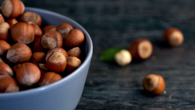 unpeeled hazelnuts are poured out of it on wooden background - nutshell stock videos & royalty-free footage