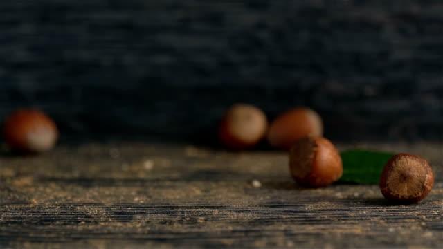 皮が付いたままのヘーゼル ナッツは、木製の背景にそれを注がれる - ナッツの殻点の映像素材/bロール
