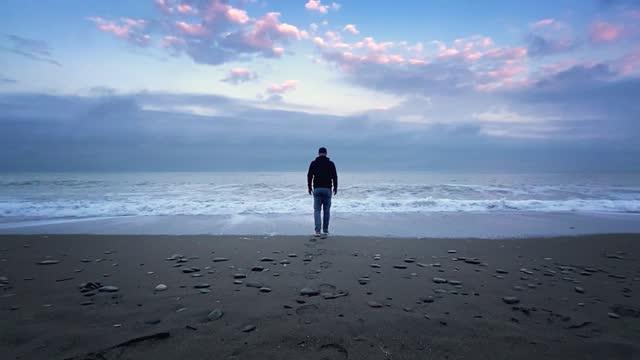 vídeos de stock, filmes e b-roll de homem irreconhecível caminha até o mar ao pôr do sol - símbolo