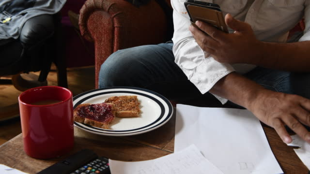unrecognisable man with tea, toast, pencil and phone making notes - pencil isolated stock videos & royalty-free footage