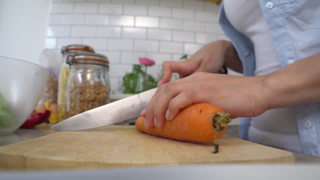 Unrecognisable woman taking vegetables out of the fridge to chop