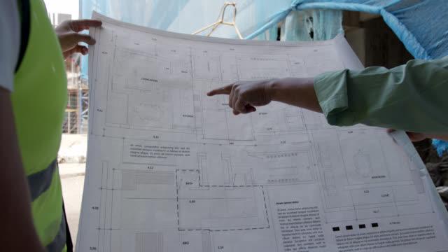 設計図をチェックする建設現場で認識できない建築家とエンジニア - 土木技師点の映像素材/bロール