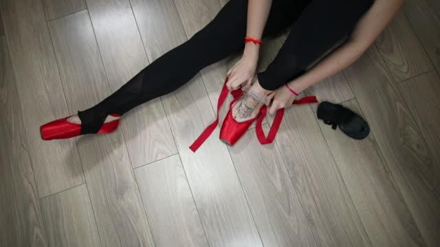 Unrecognizable Ballerina tying ballet shoes