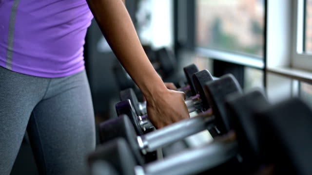 unrecognizable black woman grabbing free weights at the gym - sollevare video stock e b–roll